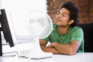 Young man in office with fan